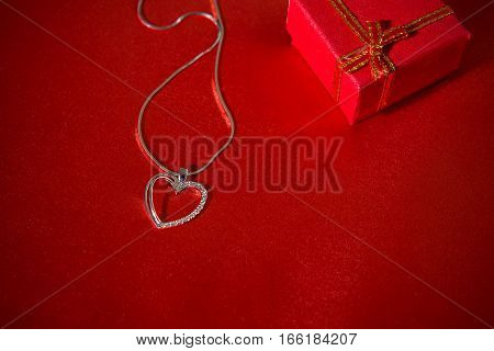 Heart pendant on a red satin background and a gift box