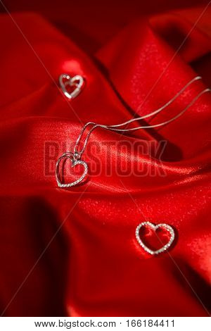 Silver heart pendants over a red satin background