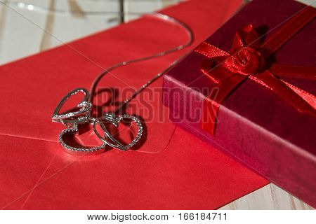 Closeup of silver heart pendants on a red envelope and gift box over a wooden background