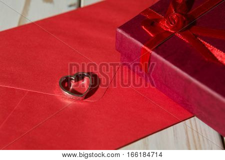 Closeup of a silver heart pendant on a red envelope and gift box over a wooden background