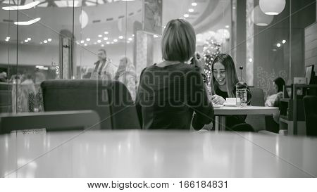 Woman In Black Dress Sitting In A Chair At A Table In A Cafe Interior. Cheerful Conversation Between