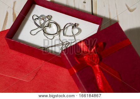 Closeup of silver heart pendants in a red gift box and a red envelope over a wooden background