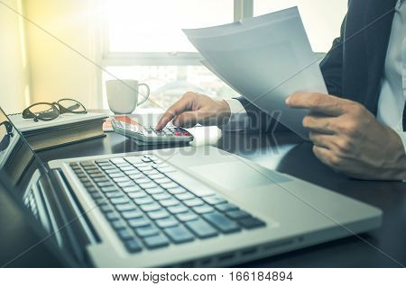 Man Using Calculator With Financial Document.