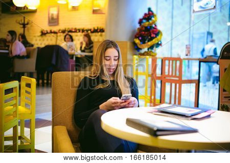 Woman In A Cafe. Young Girl Sitting At A Table In A Black Dress And Looking Into The Smartphone