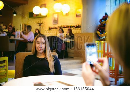 Woman In Cafe. Young Girl In Black Dress Sits At Table Smiling Girlfriend Makes Photo On Smartphone