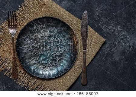 Top View Of Dark Ancient Handmade Cast Iron Plate With Cutlery On A Black Cement Background With Cop