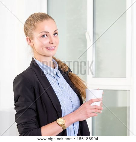Young businesswoman in modern bright office with list of tasks in her tablet drinking hot morning coffee. Business concept
