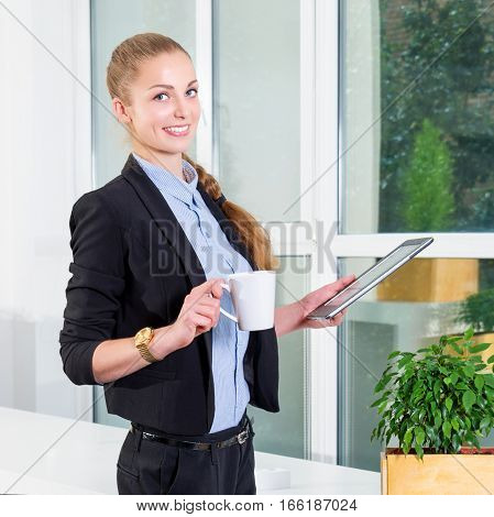 Young businesswoman in modern bright office holding the tablet with a list of tasks and drinking her morning coffee. Business concept of office work