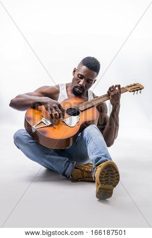 Muscular black man playing guitar, wearing jeans and white tank-top