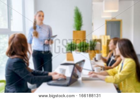 Blurred background. Pretty young business woman giving a presentation in conference or meeting setting. People and teamwork concept - happy creative team in office. Women in businness