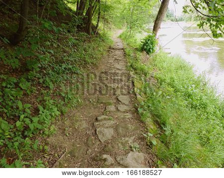 Photo of an old cobblestone pathway next to a river
