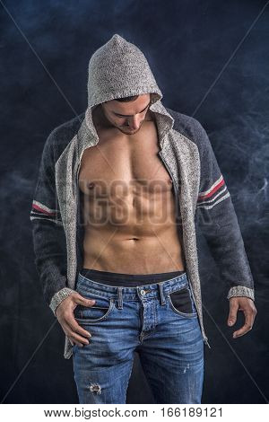 Confident, attractive young man with open vest on muscular torso, ripped abs and pecs. On dark background poster