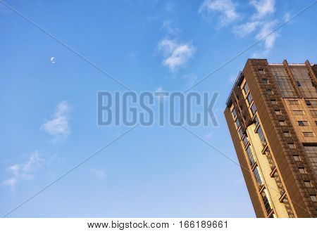 The exterior of a modern building under a waning moon on the island of Macau China on a sunny morning as a jet flies by.