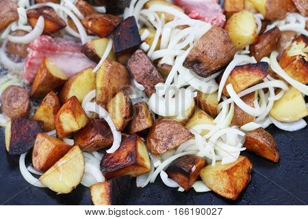 Frying potato and onion in sunflower oil on big pan. Cooking potatoes