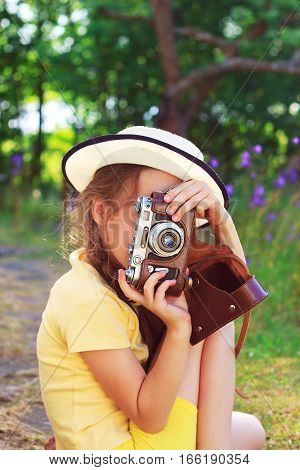 Cute little girl in retro outfit taking pictures with old film camera. Supporting creativity learning by doing creative leisure for children. Photo in retro style. Pretty child in nature. Outdoors portrait.