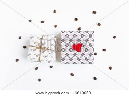 Handmade gifts on white background decorated with heart and coffee beans. Rustic style cute paper DIY decoration. Valentine's day or other holiday concept. Flat lay top view
