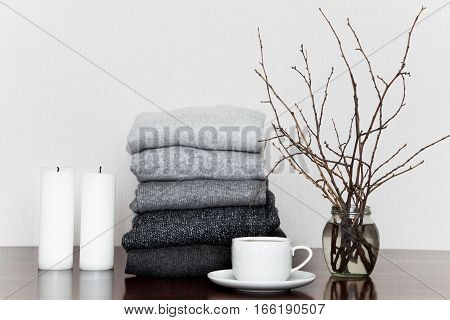 Pile of grey knitted sweaters on wooden table decorated with candles cup and a vase with branches. Winter clothes in all shades of grey minimalism at home or in clothing store