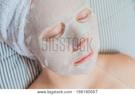 Young Red-haired Woman Relaxing On A Bed. Sheet Mask On Her Face