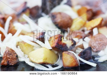 Frying potato and onion in sunflower oil closeup on big pan. Cooking potatoes