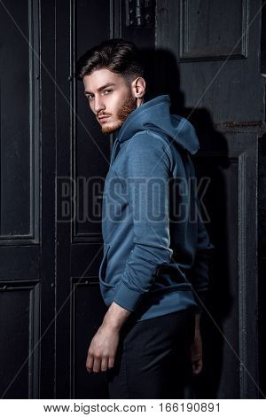 Handsome fashion model man posing wearing hoodies jacket near the wooden wall
