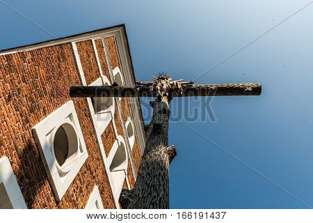 Nesvizh Belarus - September 12 2016: The cross with the crucifixion of Jesus Christ and the church bell tower in the territory of the The Corpus Christi Church