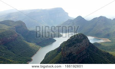 View from Lowveld Viewpoint to the Blyde River Canyon at the panoramic route in South Africa, deep gorge surrounded by striking rocks of red sandstone, natural wonder in Mpumalanga province
