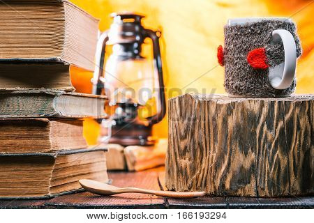 Teacup wearing wool sweater on wood stand. Book stack next to it on the table. Lamp on the background. Concept of homework in relaxing atmosphere