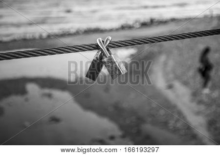 Pair of coupled padlocks as symbol of eternal love hanging on bridge metal cable in front of beach in black and white. Romance concept. Blurred background with silhouette of young girl.