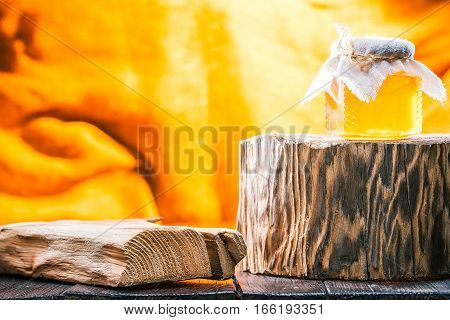 Honey in little glass jar on rustic wood stand over fire light