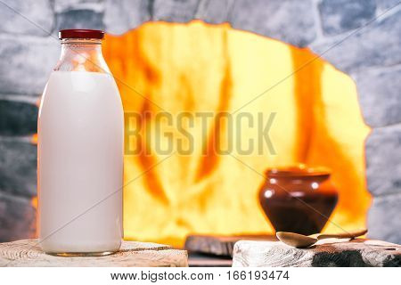 Bottle of milk on the serving board. Clay pot  in oven hearth on the background