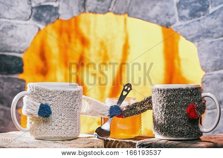 Tea mugs in sweaters taking the teaspoon out each other. Stone fireplace hearth on the background