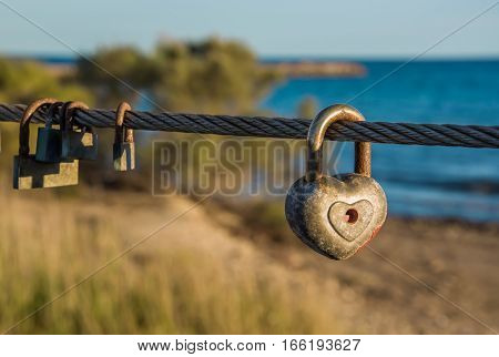 Old rusty padlocks one of these heart shaped hanging on bridge rope in front of beach. Love sign and romance concept. Blurred background. Horizontal.