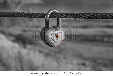 Heart shaped padlock with peeled off red paint in enlarged view as symbol of eternal love hanging on metal cable in black and white composition. Romance concept. Blurred background.