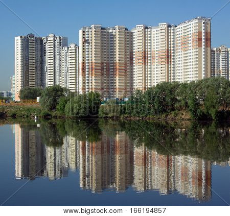 Cityscape with many new constructed block of flats in new district after river over clear blue cloudless sky in summer day