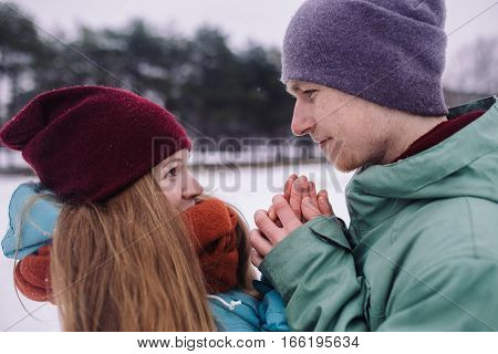 Happy couple playful together during winter holidays vacation outside in snow park. young man and woman hugging outdoor. young man heats hands of frozen girl