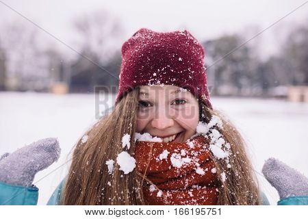 young woman with snow flakes on a burgundy scarf. young woman having fun with snow in winter park.