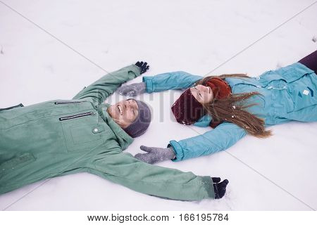 Happy Young Couple having fun in Winter Park. young man and woman lying on the snow. Family Outdoor. people season love and leisure concept