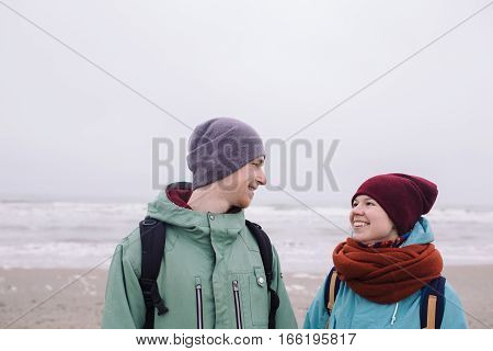 Happy young Couple on winter beach. young man and woman smiling and looking at each other