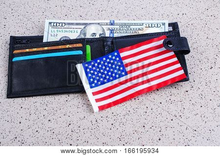 One banknote hundred dollars black purse and an American flag. On a gray background.