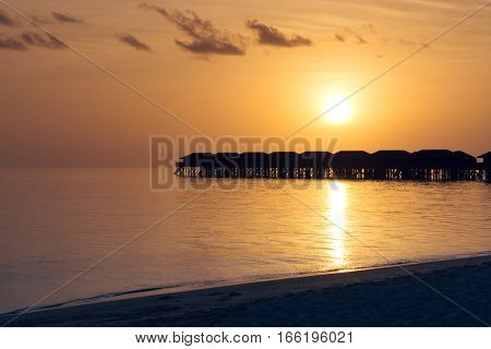 Silhouette beautiful tropical Maldives resort hotel and island with beach and sea on sunset sky for holiday vacation background concept - Boost up color Processing