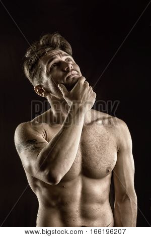 Handsome muscular, shirtless man looking up thinking with doubtful expression, isolated on black