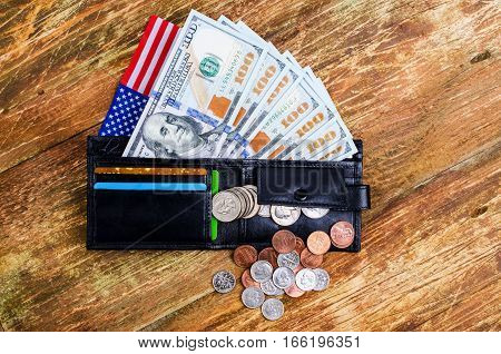 Banknotes hundred dollars in wallet american flag and different coins. On a wooden surface.