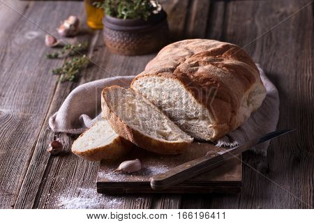 freshly baked crusty homemade ciabatta bread on wooden cutting board with herbs and garlic