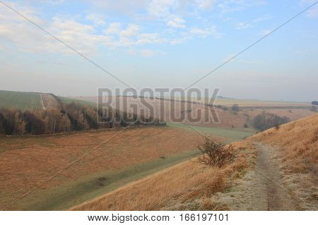 English winter landscape with a trail through the frozen grasses and woodlands of a scenic valley in the Yorkshire wolds countryside in January