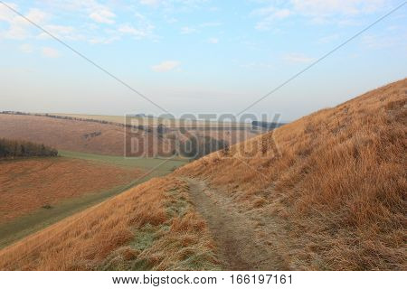 English winter landscape with a frozen trail through a grassy valley in the scenic countryside of the Yorkshire wolds in January