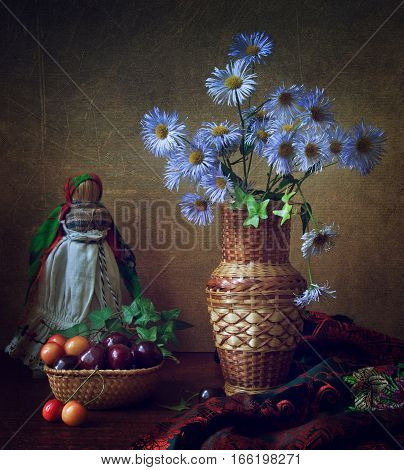 Beautiful bouquet with purple flowers in a straw vase with sweet cherry fruits and a doll made of rags