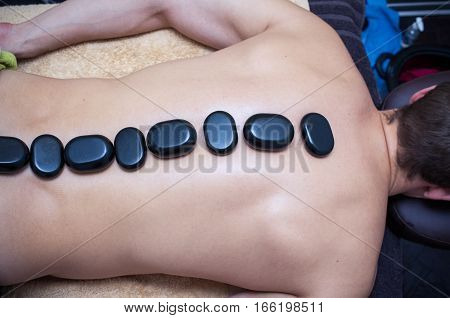 Photo of the man's back, who is getting massage and stone therapy in salon