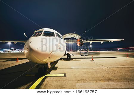 Busy airport in the night. Preparation of the turboprop airplane before flight.