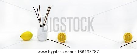 Aromatic sticks for home in white ceramic vase with fruits. Isolated on white