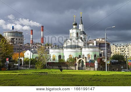 Moscow contrasts - building in the style of constructivism the smoking chimneys of the power station and the old Orthodox Church next to each other against the gray autumn sky.